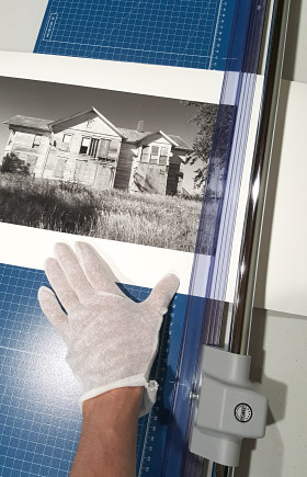 image of gloved hand adjusting black and white print on rotary cutter