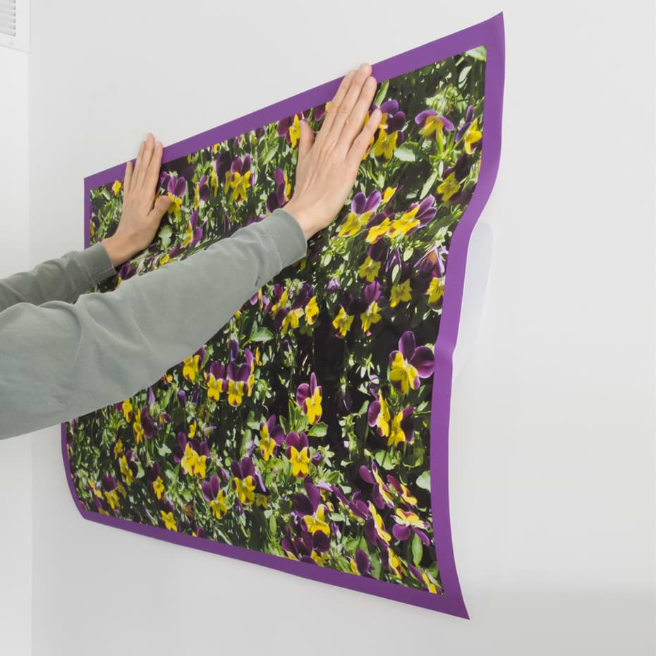 person applying peel and stick print to a wall